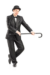 Full length portrait of a male magician holding a cane