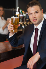 Businessman holding a pint of beer smiling at camera