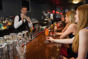 Handsome bartender making cocktails for attractive women
