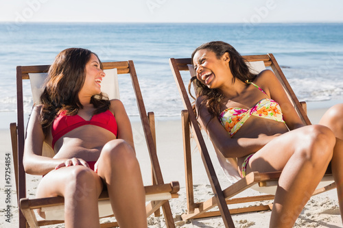 Cheerful beautiful friends relaxing on their deck chairs