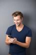 lächelnder mann tippt auf smartphone