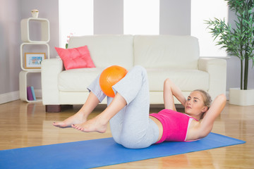 Sporty calm blonde doing sit ups holding ball between knees