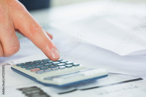 Close up of finger using calculator