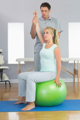 Physiotherapist correcting patient sitting on exercise ball