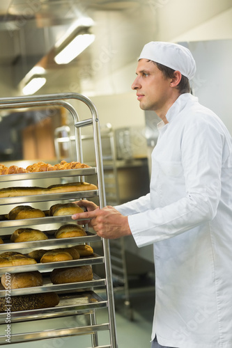 Handsome young baker pushing a trolley
