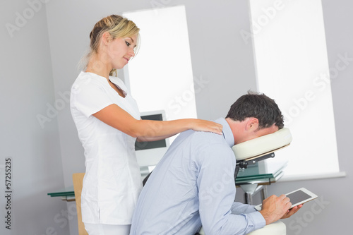 Masseuse massaging clients neck in massage chair