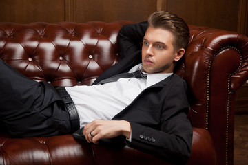 stylish man in a suit lying