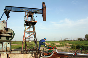 oil worker check pump jack pipeline