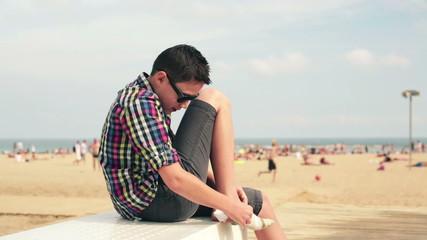 Boy putting on socks by the beach