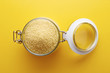Raw cous cous on a glass jar on yellow background