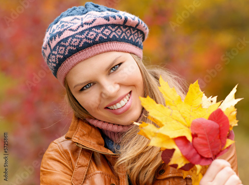 Young attractive woman enjoying fall season on nature.