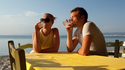 Young couple enjoying drinks at the seaside