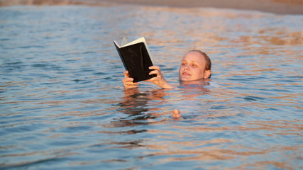 Woman smiling as she reads a book while swimming