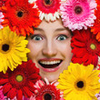 Happy smiling girl with flowers around her face. Gerbera daisy