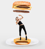 Large cheeseburger falling on a fit young woman