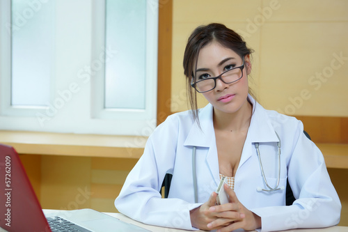 Attractive young female doctor sitting at desk in office