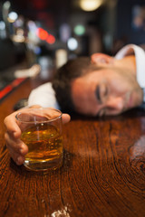 Drunk businessman holding whiskey lying on a counter