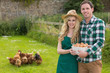 Young couple holding a basket filled with eggs in their garden
