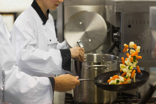 Two chefs working in a busy kitchen