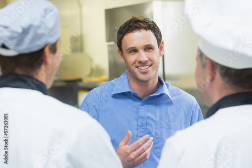 Young smiling manager talking to the staff