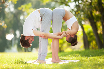 Couple Yoga, man and woman doing yoga exercises in the park