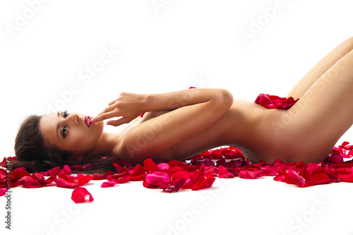 slim woman lying on red roses petals over white