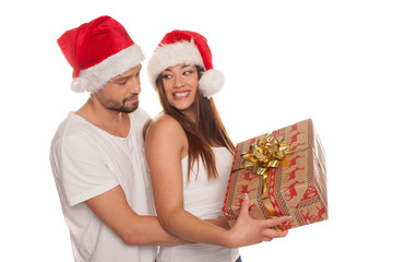 Couple looking through frame wearing Santa hats