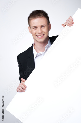 Smiling business man holding blank poster.