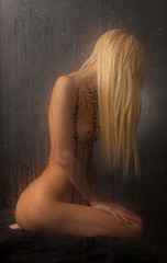 Naked blonde sitting behind a wet glass on a black background.