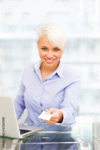 Businesswoman is giving her businesscard while smiling