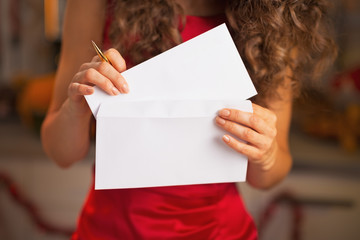 Closeup on woman putting christmas letter into envelope