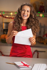 Housewife in red dress putting christmas letter into envelope