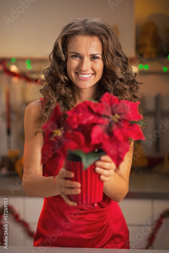 Happy young woman in red dress holding christmas rose in kitchen