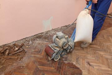 Home renovation worker polish parquet floor, grinding machine