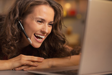 Happy young woman having christmas video chat on laptop
