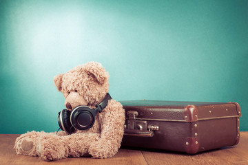 Retro teddy bear with headphones sitting near old suitcase
