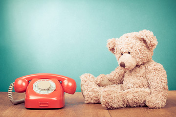 Retro red telephone and Teddy Bear near mint green wall