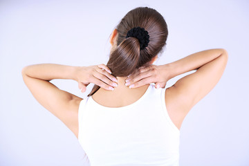 Young girl and pain in neck gray background