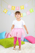 Little girl dancing on bed in room on grey wall background