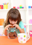 Little girl eating cookies sitting at table in room
