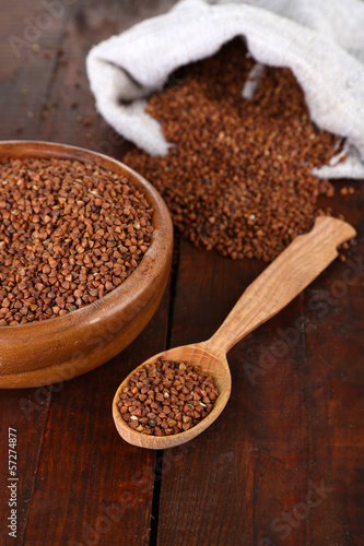 Buckwheat groats in bowl and  wooden spoon closeup