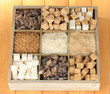 Different types of sugar in wooden box on table close-up