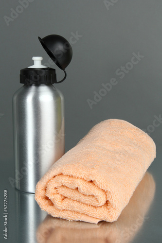 Sports bottle and towel on grey background