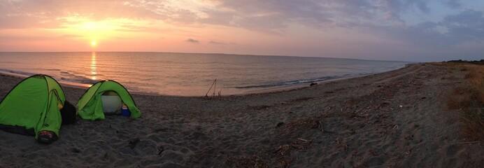 lever de soleil sur un bivouac au bord de la plage