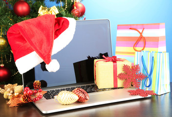 Laptop with gifts on table on blue background