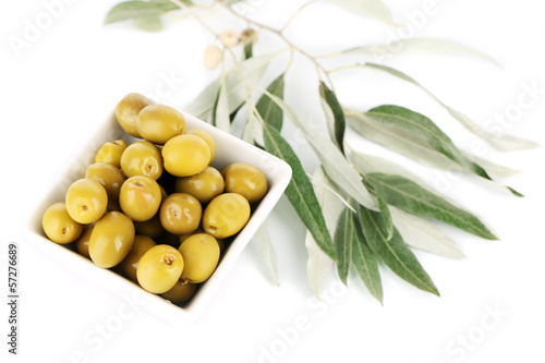 Olives in bowl with branch isolated on white