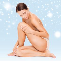 beautiful naked woman touching her legs