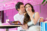 Young couple enjoying their time in ice cream parlor poster