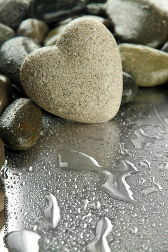 Grey stone in shape of heart, on light background