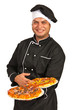 Smiling chef serving pizza